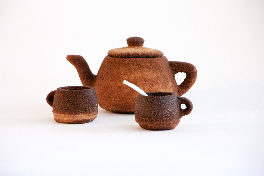 The low, rounded teapot and teacup are a rich reddish brown color with a coarse, gritty texture.