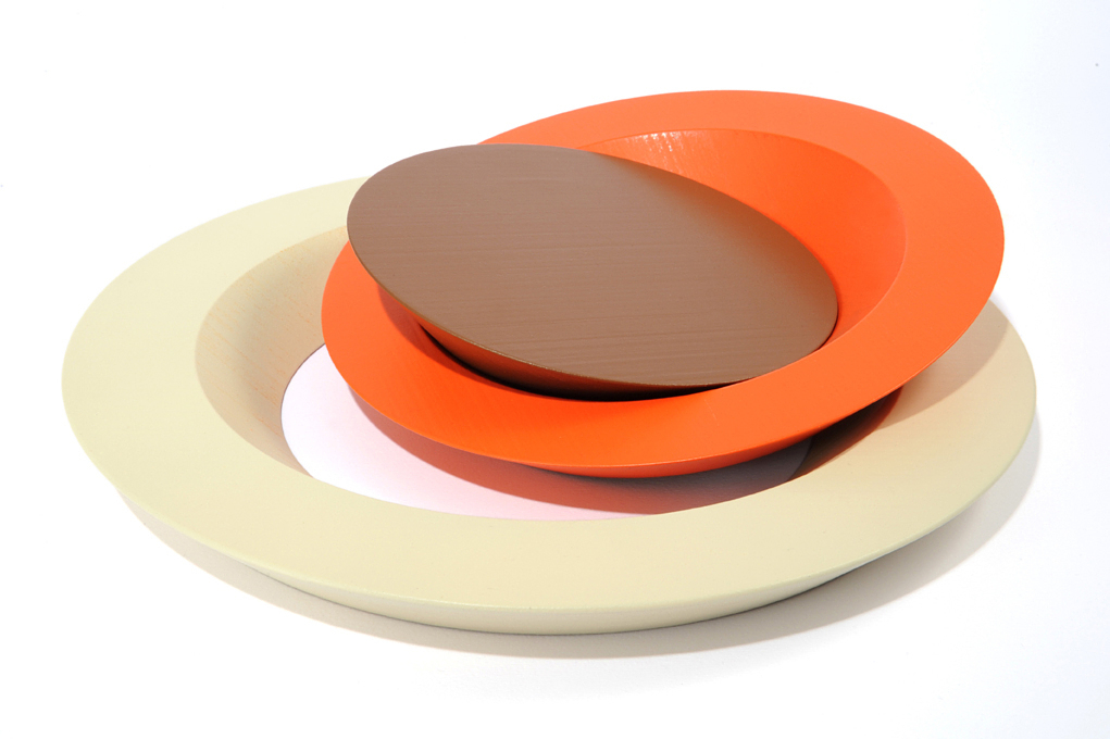 A cake platter consists of concentric circles—one orange and one cream—nested around a chocolate brown center plate.