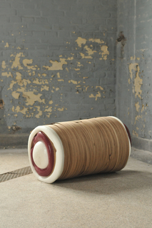 Wood logs are suspended in resin, which has been cut to reveal the sliced wood.