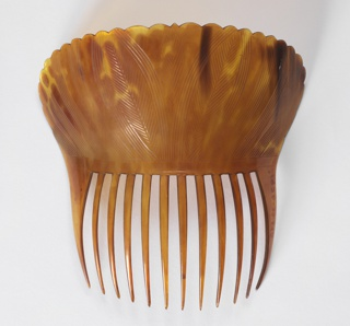plain curved comb with scalloped edges and long teeth, Shell is divided into equal upper and lower portions and carved from light amber color tortoiseshell