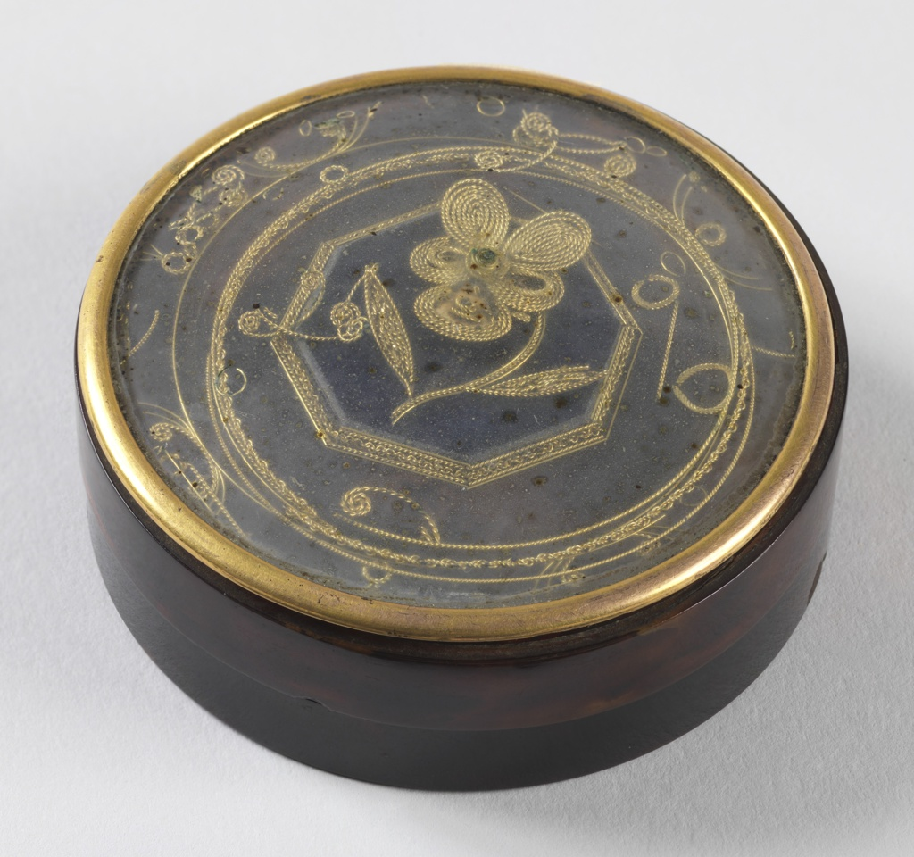 Dark circular tortoiseshell box with gold border around edge of lid and an illustration of a simple flower and shapes surrounding the central motif on top of the lid