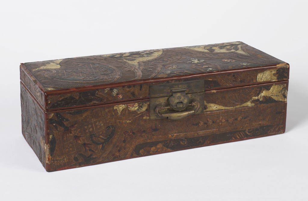 Rectangular box in red-brown lacquer. Faced with Dutch leather embossed and tooled; decoration of scroll-enclosed diapered fields in gold; flowers on white or brown painted field. Brass hinges, mount and clasp. Yang-Yin design incised on mount; clasp with pair of sea horse heads and scale pattern.