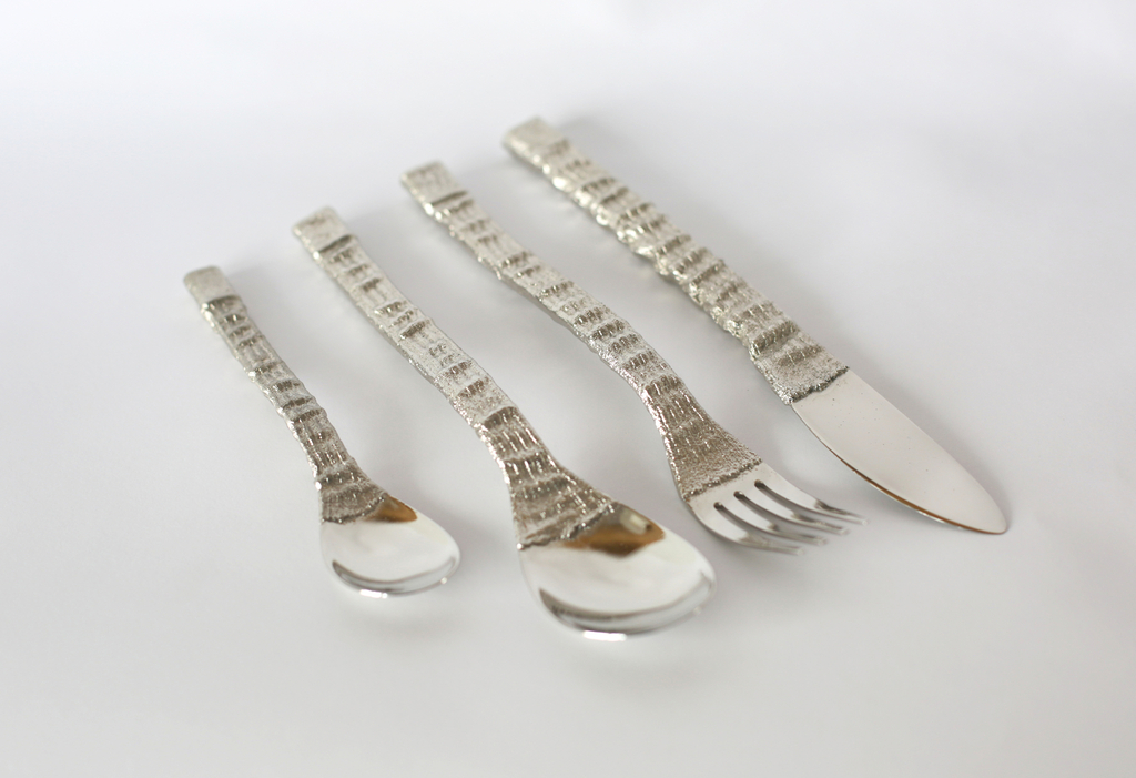 Two spoons, a fork, and a knife have a rought texture that was made from casting knitted textiles.