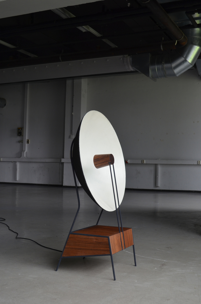 A cone-shaped speaker points inward at a larger parabolic bowl, which resembles a horn on a gramophone. The bowl directs sound waves back toward a listener.