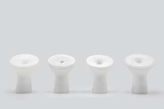 Four white, cone-shaped speakers, each the size of a large coffee cup, have different textures, ranging from smooth and hard to rough and fuzzy.