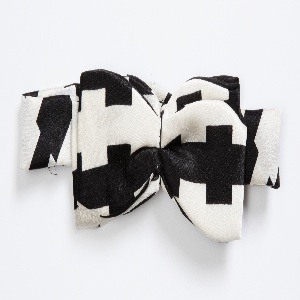 White satin bow tie with a black geometric pattern.