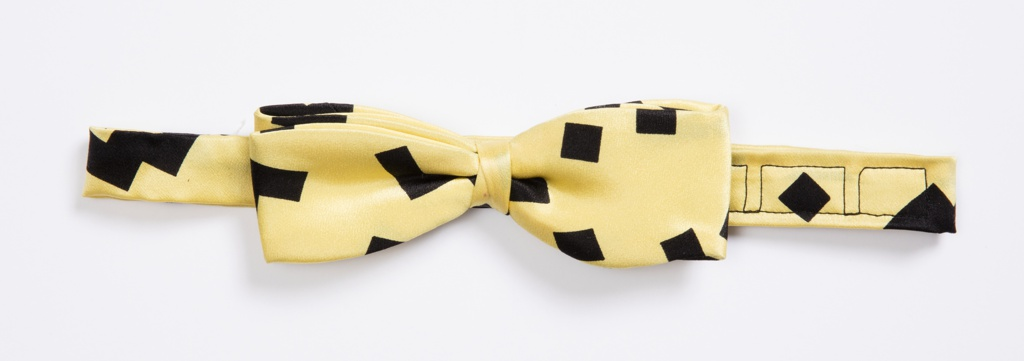 Yellow satin bow tie with a pattern of black zigzags, squares and L-shapes.