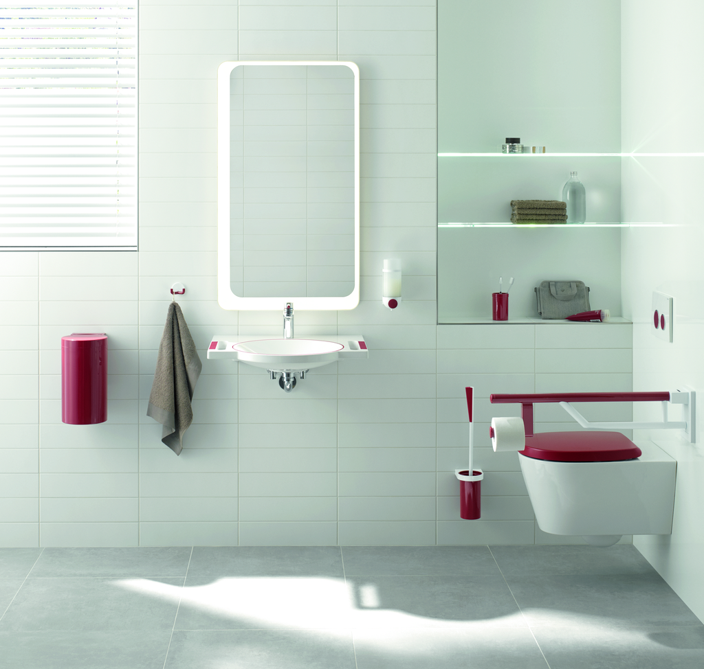 A white sink in a white bathroom has red details. Other elements in the bathroom are also red, including the toilet brush, the towel rack, and the button on the soap dispenser. The red elements are easy to see and identify for people with dementia or low vision.