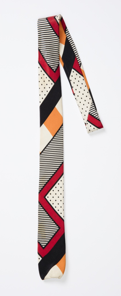 Necktie with bold graphic and geometric patterning. Black, dark red and orange are used in stripes, dots and diagonal bands on an off-white silk ground.
