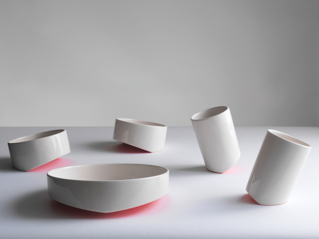 A white ceramic bowl, cup, and plate each have a slanted bottom, making them tip one way or the other. The undersides are neon pink, casting a soft glow on a table.