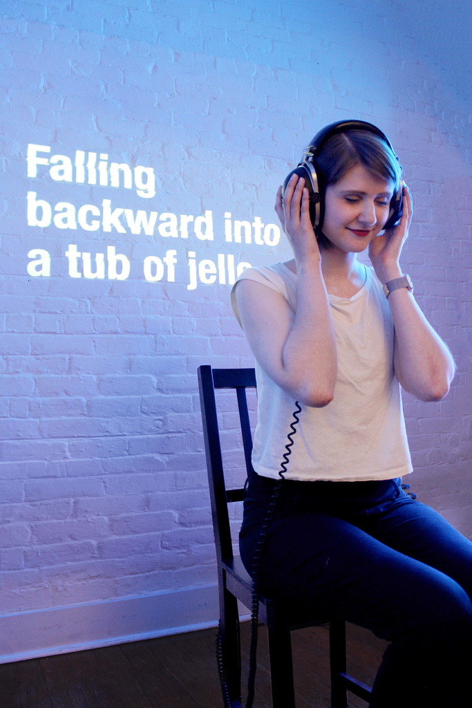 "A young woman wearing a headset sits in a chair. A phrase is projected on the wall behind her: ""Falling backward into a tub of jello."""