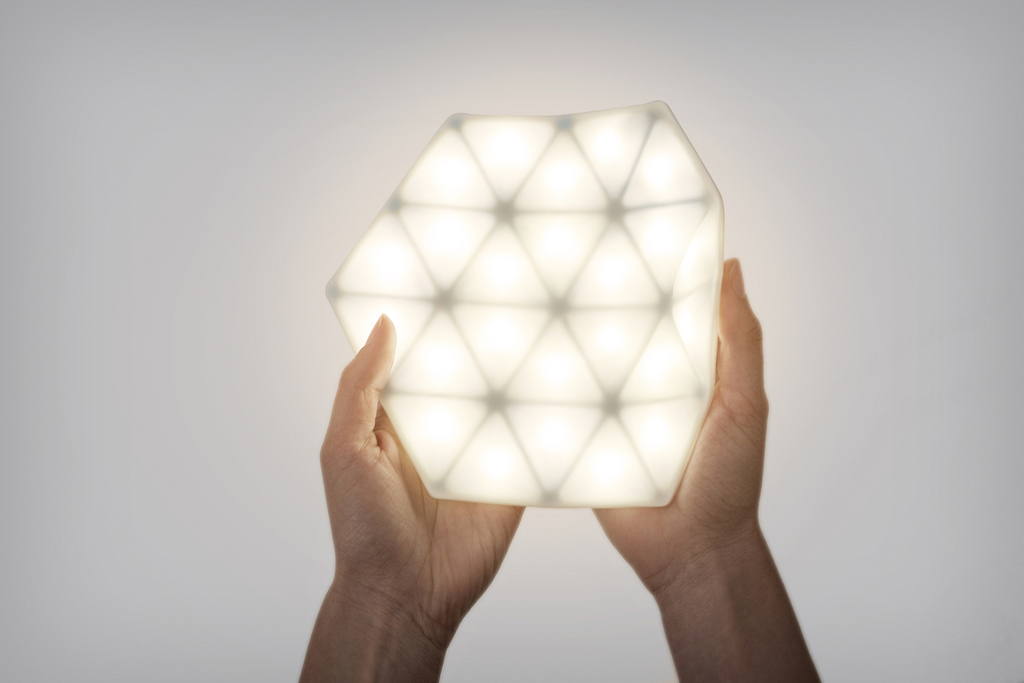 A soft, bendable hexagon is made of glowing, quilted silicone. It has twenty-four LEDs hidden within.
