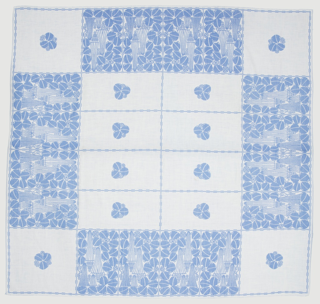 Blue and white tablecloth with a central section containing eight blue rectangles, each with a single stylized floral element in white. Four squares with the same isolated floral motif are at each corner with rectangles between containing a dense arrangement of geometrical and floral elements.