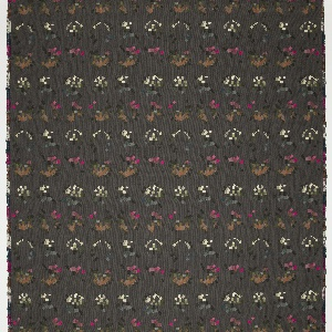 Woven textile with a charcoal gray ground and a pattern of fragmented color wheels, made up of small squares of greens, gray-blues, browns, pinks, and off-whites.
