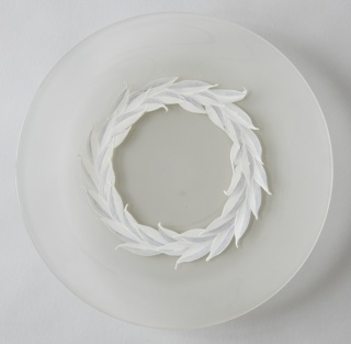 Round plate with a concentric foliage (laurel) motif band painted in white and mauve. Inner circle is clear glass and the outer circle from the outer edge of the painted band to the rim of the plate is sandblasted on the reverse side of plate.