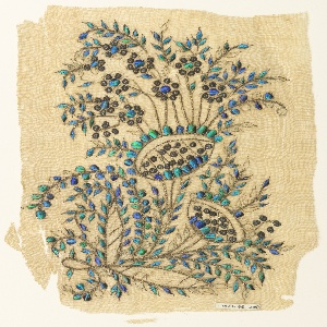 Off-white cotton sheer ground with embroidered design of a stylized floral spray with two large blossoms and numerous small ones curving to the left.  The vines are executed in gold foil strips, the small flowers in gilt sequins, and the leaves in beetle elytra.