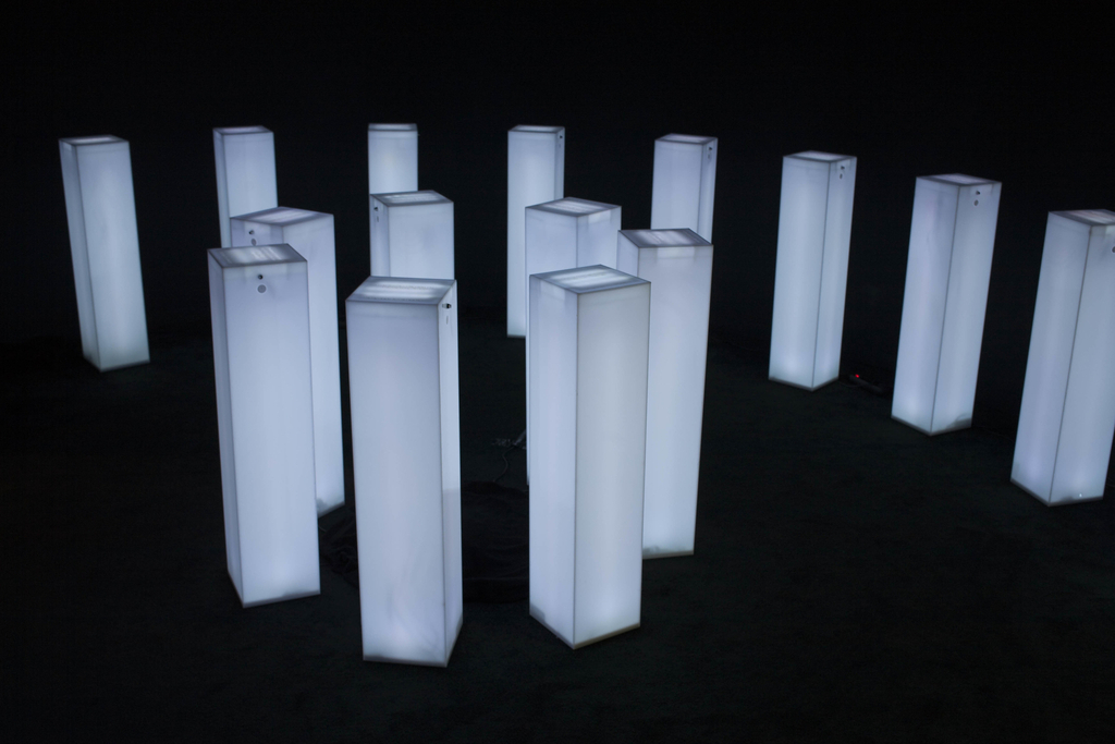 "Six low, white pillars glow with light. On the top of each pillar, a line of text describes a complex emotional state, such as ""a moment of collective déjà vu.\"" A button releases a unique scent that rises through the letters."