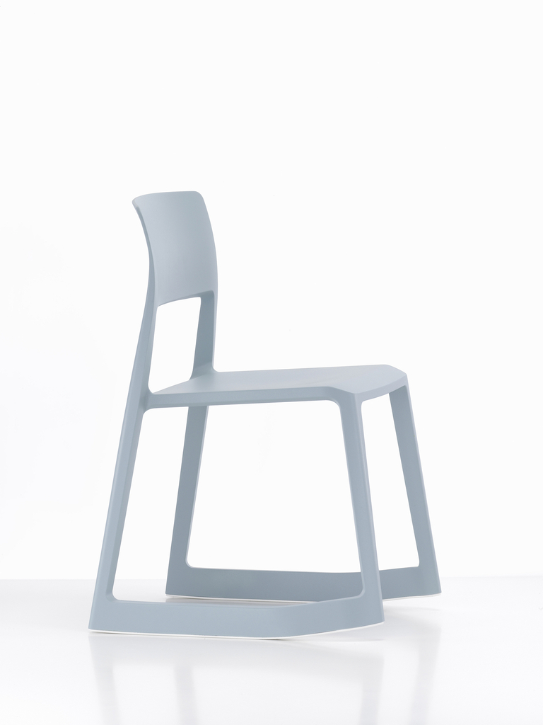 A blue plastic chair has a blade-like base that lets it tilt backward and forward.