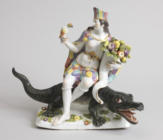 """America"" female figure with feather skirt, mantle and headdress, holding parrot and cornucopia; seated on alligator facing right."