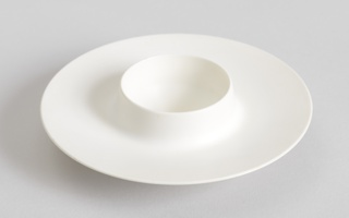 Circular form of white melamine with wide, tapering everted rim surounding circular well with lip tapering to fine edge; low circular foot ring.