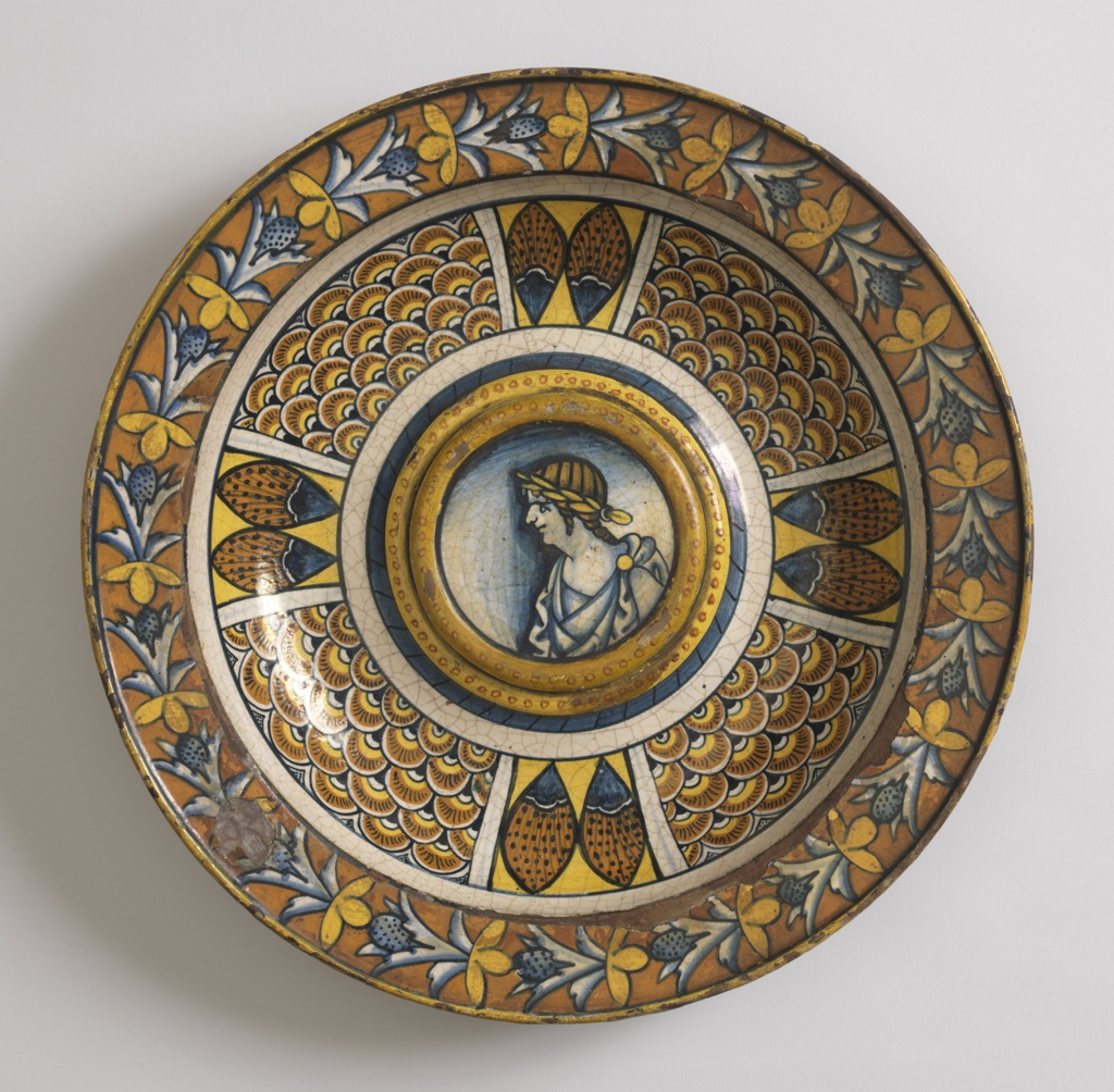 On the raised center, a profile busy of a man dressed as a Roman emperor. The segmented border shows peacock feathers and scale ornaments, the rim shows floral designs in blue and yellow on an orange ground.