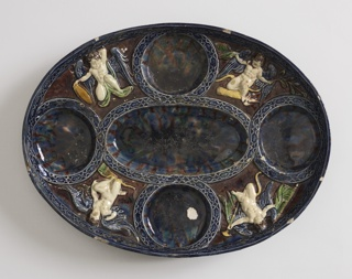 Oval dish with curving sides, on oval molded foot. In center, oval depressions with four circular depressions tangent at mid-point of sides and ends. Edge of dish and depressions are outlined by raised patterned bands of dark blue. Spandrels between four circular depressions are glazed in red-brown, with relief figures of winged putti bearing military attributes. Mottled glazes in depressions and on reverse.