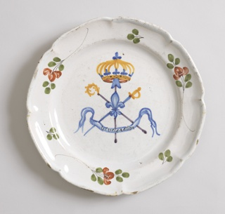 Octagonal scalloped marly, decorated with alternating large and small sprays of foliage. In center, crossed crosier, sword and spade with fleur-de-lis at point of crossing; above, royal crown; below, banderole inscribed: Viva la nation. Blue, yellow and violet in center; green and red on marly.