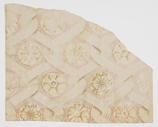 Piece of irregular shape giving full repeat. Opposed interlacing chevrons, set vertically, with rosettes of varying design, in grisaille with accents of cream and white. Grey ground with vermiculation of red.