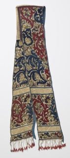Long narrow head covering or hood made of two straight pieces attached at the top and back with bands of hand twisted linen cord, the long sides allowed to hang free. The foundation is loosely woven cotton, embroidered in large-scale allover design of spiky flowers and foliage. Red, blue, violet and shades of yellow and green are all outlined in dark brown. Design is arranged in two panels, divided by horizontal bands of ornaments of drawn work and white embroidery in simple star design. Fringed at ends with threads from foundation cloth, each ending in a pink tassel. Edges bound in blue silk.