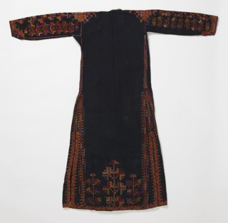 """Long coat-shaped dress of heavy black cotton, embroidered in colored silks of red, green, white, blue and orange. Long fitted sleeve embroidered entire length and around cuff. Robe closes in front with flap to close over, open at side. Embroidery largely in geometric pattern with large stylized leaf form. All seams and edges embroidered. Edges faced inside with printed cotton, """"paisley"""" cone shapes on red; may be remains of lining."""