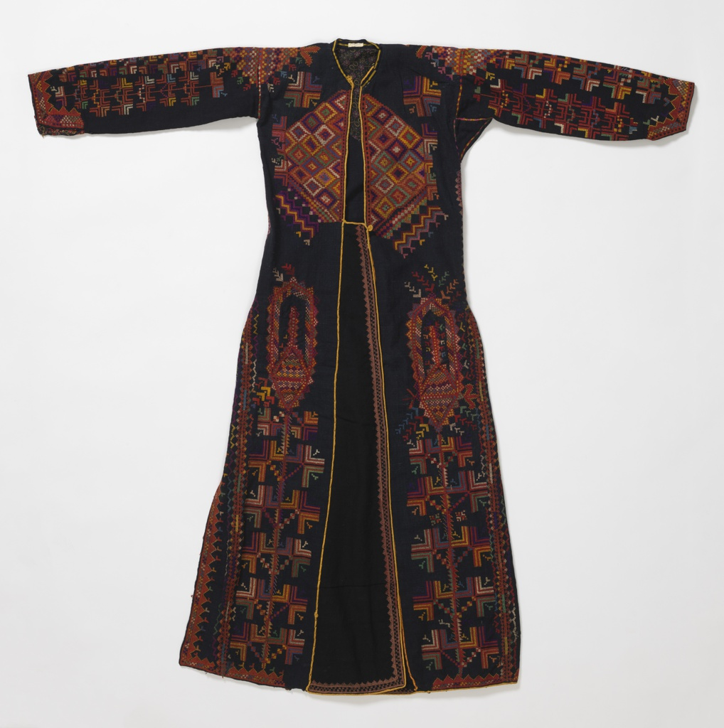 "Long coat-shaped dress of heavy black cotton, embroidered in colored silks of red, green, white, blue and orange. Long fitted sleeve embroidered entire length and around cuff. Robe closes in front with flap to close over, open at side. Embroidery largely in geometric pattern with large stylized leaf form. All seams and edges embroidered. Edges faced inside with printed cotton, ""paisley"" cone shapes on red; may be remains of lining."