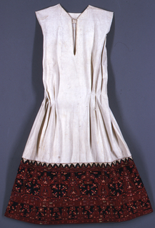 Woman's chemise with a plain white cotton top, intended to be worn under an embroidered blouse. The bottom is heavily embroidered in dark polychrome colors in a highly formalized floral design.