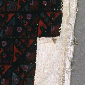 Plain woven natural cotton embroidered with dyed wool in black, purple, blue, red and bright green. Pattern shows stepped squares, each divided in half diagonally and containing circles and diamonds. At right, larger squares with circles and darts.