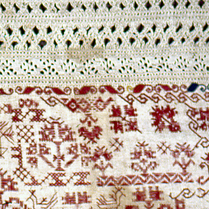 Sampler divided into two columns. On the left, bands of withdrawn element work in white on white; on the right, withdrawn element, and spot motirs in red on white.