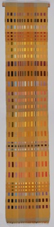 Long, narrow, woven hanging with a multicolored grid of rectangles on an ochre ground.