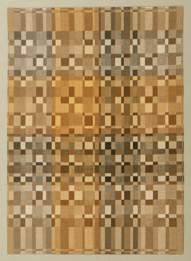 Rectangular weaving with an abstract geometric pattern in four quadrants divided by a cross, in shades of gray and ochre.