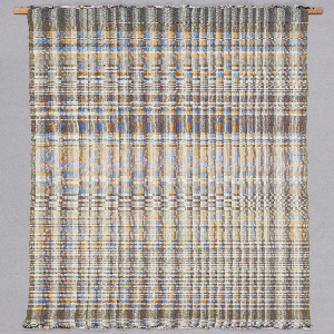 A long, narrow, rectangular weaving with an abstract geometric pattern in shades of tan, white, and blue.