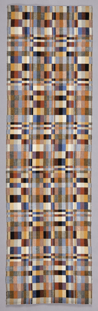 Long, narrow, rectangular weaving with an abstract geometric pattern of variously-sized rectangles in shades of black, white, gray, blue, rust, and ochre.