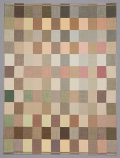 Small-scale rectangular weaving with a checkerboard pattern of squares in soft shades of brown, tan, green, and pink.