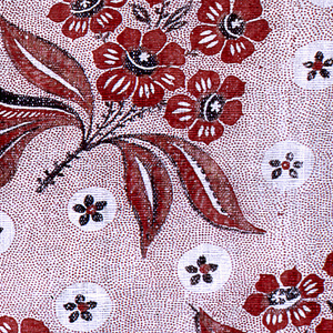 Offset repeat of a flowering branch surrounded by white circles containing small blossoms. Pattern is in red and black on a red picotage background.