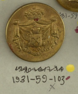 """X-cross shown on breast pocket of double-headed eagle; cloak mantling with crown above and ribbon with """"Pour l'avenir"""" below. Brass back and shank. On reverse, """"F Debacker 36 bis Avenue de l'Opera"""".  On card 45"""