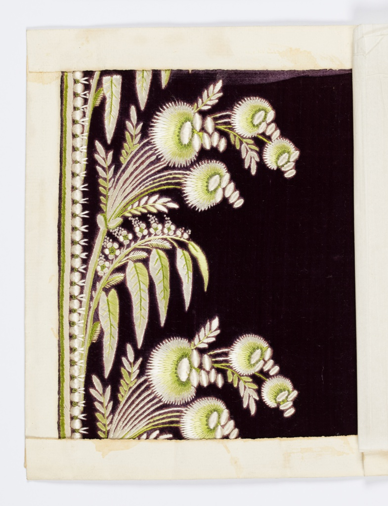 Green and white silk embroidery in a floral design on a purple ground.
