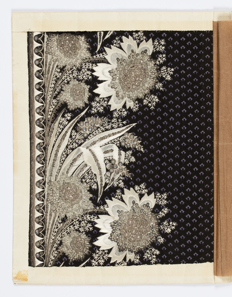 Dark purple uncut voided velvet with small triangular pattern embroidered in elaborate border pattern of flowers and leaves in silver, brilliants, and white silk.