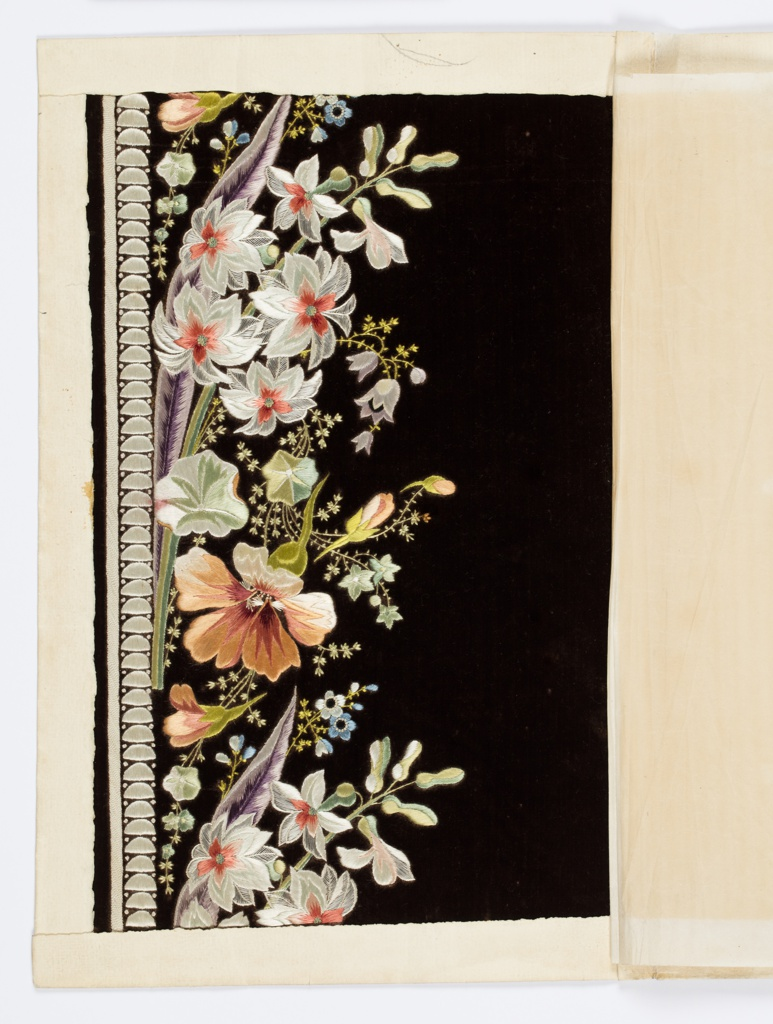 Black ground embroidered in a design of naturalistic flowers in white, violet, green, light blue and orange.