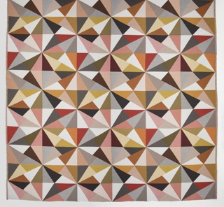 Length of woven textile with a large-scale pinwheel design of radiating triangle and diamond forms, in shades of red, orange, pink, and brown.