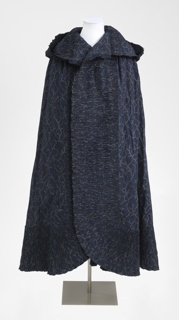 Woman's printed cotton cape, open down the front,  with a hood with a pleated ruffle all around. Fabric is dark indigo blue a discharged design in light blue, with touches of orange.