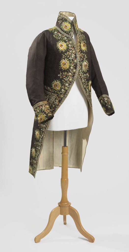 Coat of changeable brown and blue silk faille with small ovals. Embroidered with floral motif in polychrome silk.