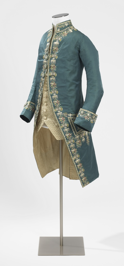 """Blue and green changeable silk coat with collar, cuffs, pockets, and front and back openings embroidered with soft polychrome silks in design of icicles with pendant sprays of minute pansies, daisies and pinks; alternating with monogram """"I.C."""", decorated with rosette and feathery foliage. Lined throughout with ivory silk plain twill. Buttons covered of same material and embroidered with minute flowers. Sleeve lining of linen plain cloth."""
