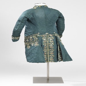 "Blue and green changeable silk coat with collar, cuffs, pockets, and front and back openings embroidered with soft polychrome silks in design of icicles with pendant sprays of minute pansies, daisies and pinks; alternating with monogram ""I.C."", decorated with rosette and feathery foliage. Lined throughout with ivory silk plain twill. Buttons covered of same material and embroidered with minute flowers. Sleeve lining of linen plain cloth."