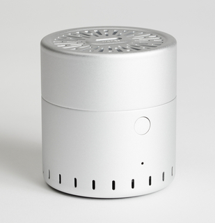 A small aluminum cylinder, about the size of a teacup, has vents on top. The vents emit smell.